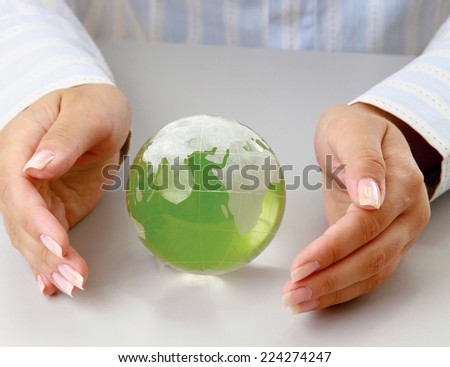 Hands holding a green earth, isolated on white background - stock photo