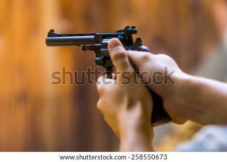 Hands holding a gun close-up - stock photo