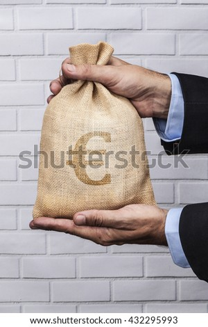 Hands holding a sack of money and white brick background - stock photo