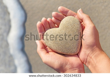Hands holding a sand in form of the heart at beach - Saint valentines day; proposal or summertime concept - stock photo
