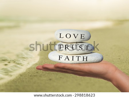Hands holding a small stack of pebbles with 'faith, trust and love' written on the top stone. - stock photo