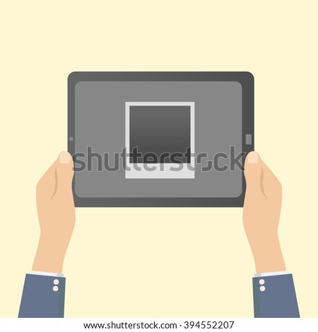 hands holding a tablet with a photo frame - stock photo