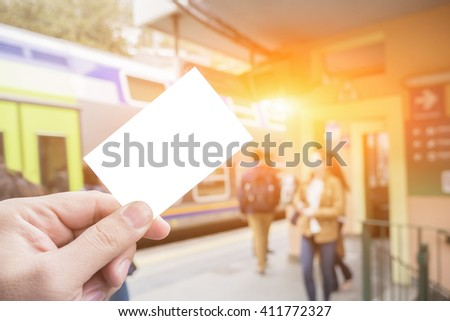 Hands holding a white business card,  close up on blurred of train station, subway Copy space, selective focus, vintage color - stock photo
