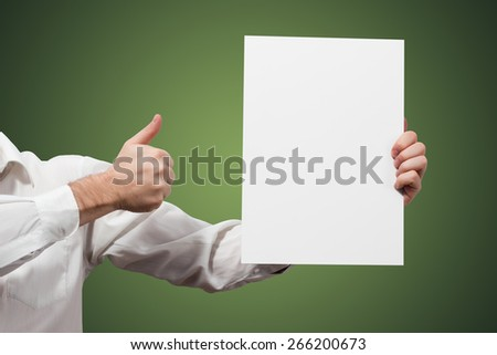 Hands holding a white paper blank isolated on green background - stock photo