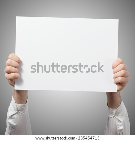 Hands holding a white paper blank isolated on grey background  - stock photo