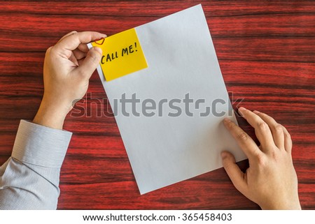 Hands holding blank page with yellow note attached by heart shaped paper clip. - stock photo