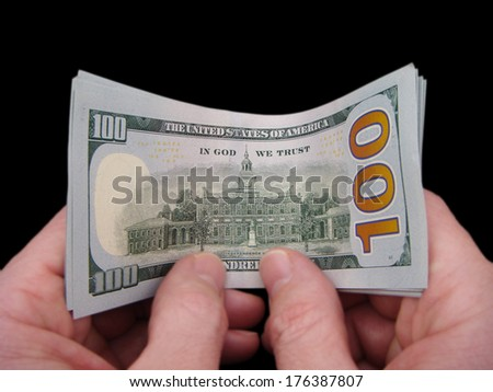 Hands Holding Brand New United States One Hundred Dollar Federal Reserve Notes, Showing The Reverse Design Curved. - stock photo