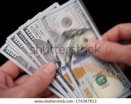 Hands Holding Brand New United States One Hundred Dollar Federal Reserve Notes, Showing Top Bill Blurred With Movement. - stock photo