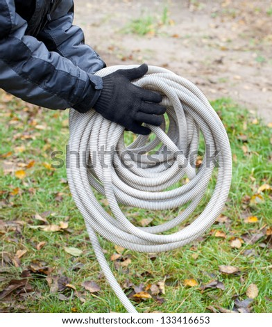 Hands holding cable corrugated hose - stock photo