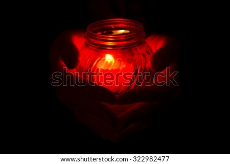 Hands holding candle during  All Saints Day. - stock photo