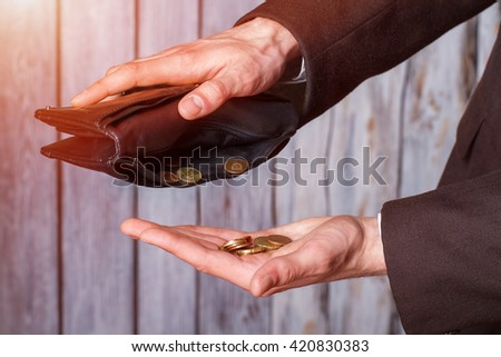 Hands holding coins and wallet. Black wallet and small coins. Not a cent more. The definition of poverty. - stock photo
