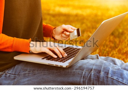 Hands holding credit card and using laptop on natural summer background. Online shopping - stock photo
