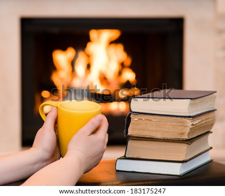 hands holding cup of coffee near the fireplace - stock photo