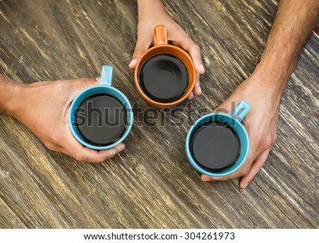 Hands holding cups of coffee over a table - stock photo