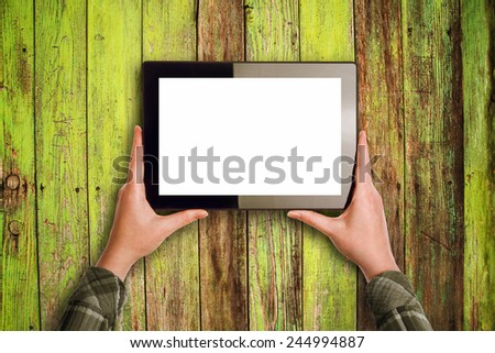 Hands holding Digital Tablet Computer with Blank White Screen as Copy Space over wooden background - stock photo