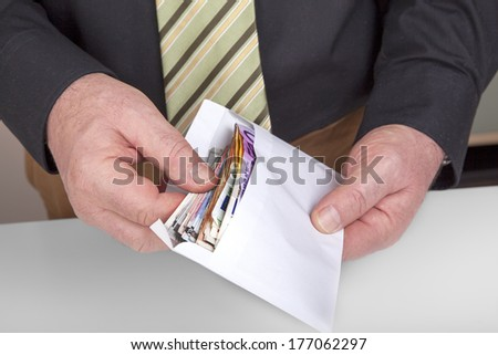 Hands holding envelope with cash - stock photo