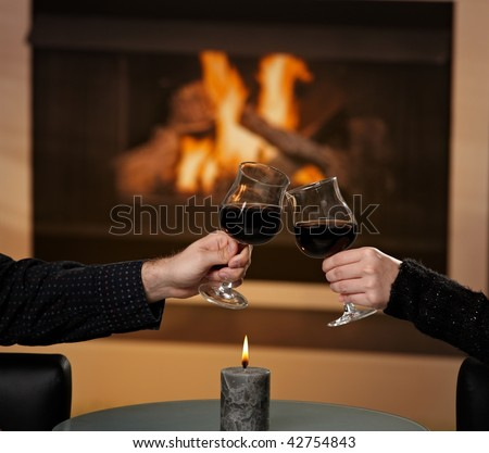 Hands holding glass of red wine, clinking in front of fireplace. - stock photo