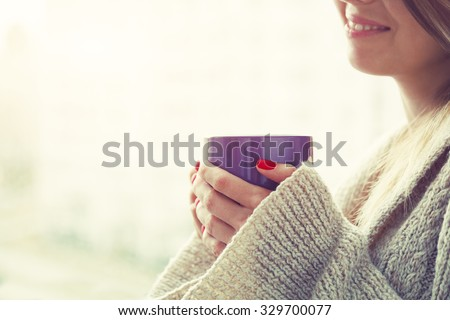 hands holding hot cup of coffee or tea in morning - stock photo