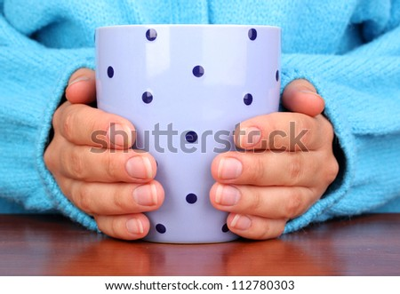 hands holding mug of hot drink close-up - stock photo