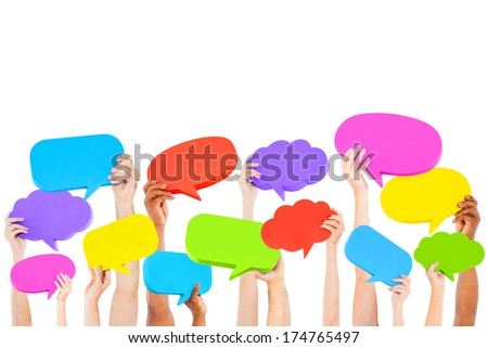 Hands holding multi colored speech bubbles. - stock photo