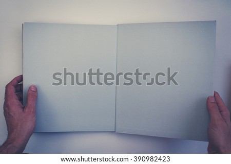 hands holding open book with blank pages   - vintage style - stock photo