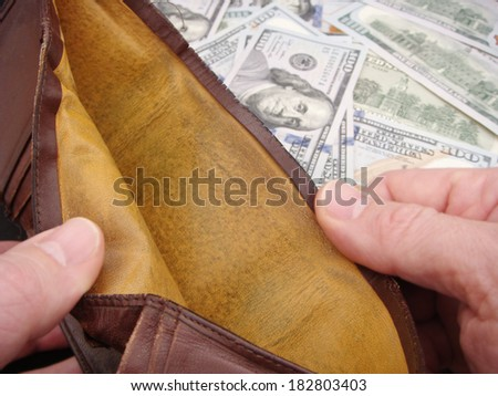 Hands Holding Open Empty Leather Wallet Over Brand New United States One Hundred Dollar Federal Reserve Notes. - stock photo