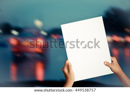 Hands holding paper.Blurred image car on the road. - stock photo