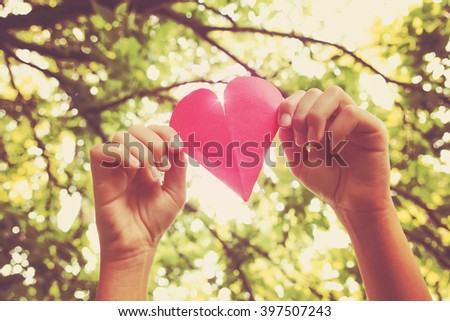 Hands holding paper heart  - stock photo