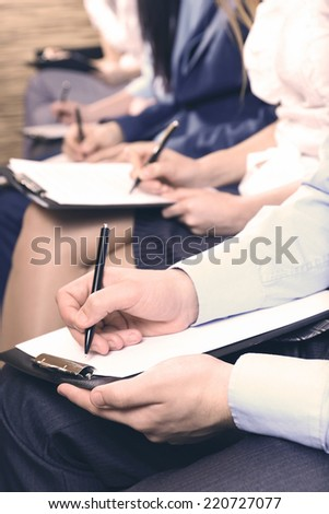 Hands holding pens and making notes at conference - stock photo