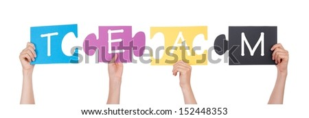 Hands Holding Pieces of a Puzzles with Team on it in the many Colors, Isolated - stock photo