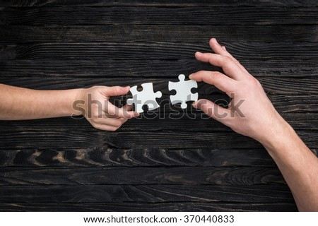 hands holding pieces of white puzzle - stock photo