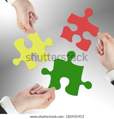 hands holding puzzle isolated on gray - stock photo