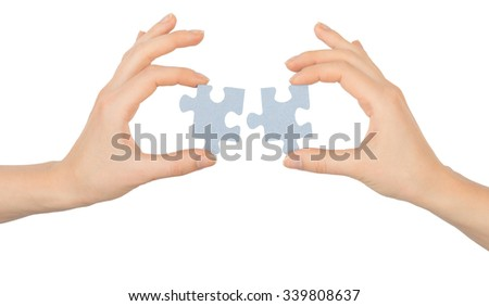Hands holding puzzle pieces on isolated white background - stock photo
