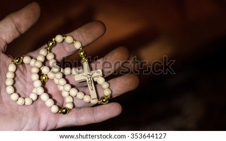 Hands holding rosary beads and cross,horizontal photo - stock photo