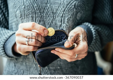 Hands holding russian rouble coin and small money pouch - stock photo