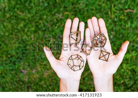 Hands holding sacred geometry - stock photo