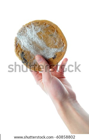 Hands holding shrink wrapped cookie isolated on white white background - stock photo