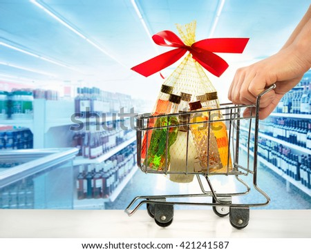 Hands holding small trolley with alcoholic beverages against background of shelves with drinks in supermarket                                      - stock photo