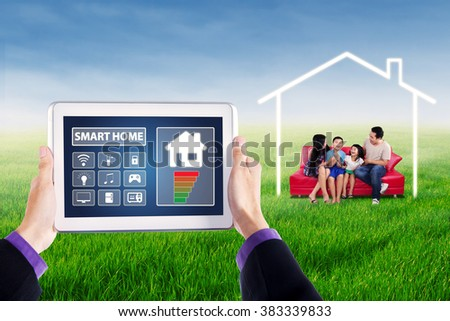 Hands holding smart home controller on the digital tablet, shot with happy family sitting on the sofa at field - stock photo