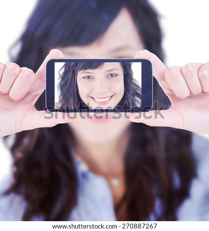 Hands holding smartphone against portrait of a smiling young woman - stock photo