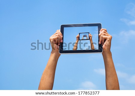 hands holding tablet in blue sky - stock photo