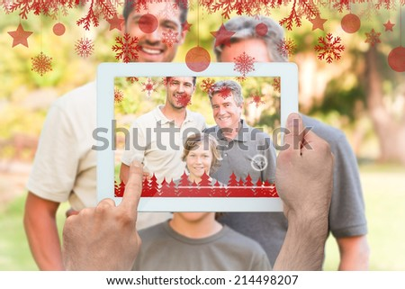Hands holding tablet pc against family looking at the camera in the park - stock photo