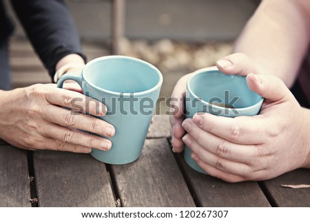 hands holding teacups coffee mugs - stock photo