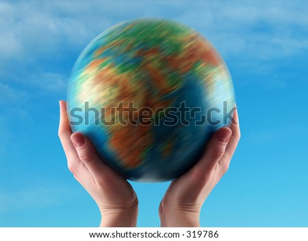 hands holding the earth in rotation, clear sky background - stock photo