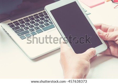 Hands holding the touch screen device laptop background - stock photo