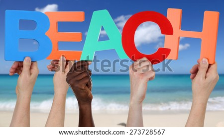 Hands holding the word beach with sand and sea in summer on vacation - stock photo