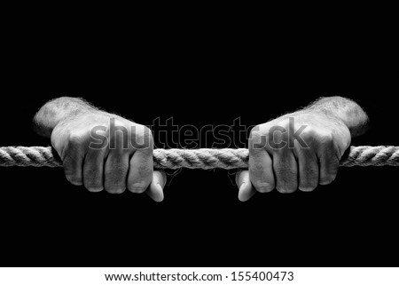 Hands holding tight rope on dark background. Salvation or redemption concept. - stock photo