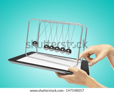 hands holding  touch pad with newton's cradle  on a blue background - stock photo