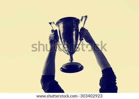 hands holding trophy up in the air with a shallow depth of field with a retro instagram filter - stock photo