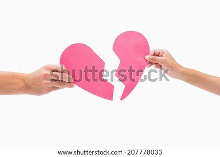 Hands holding two halves of broken heart on white background - stock photo